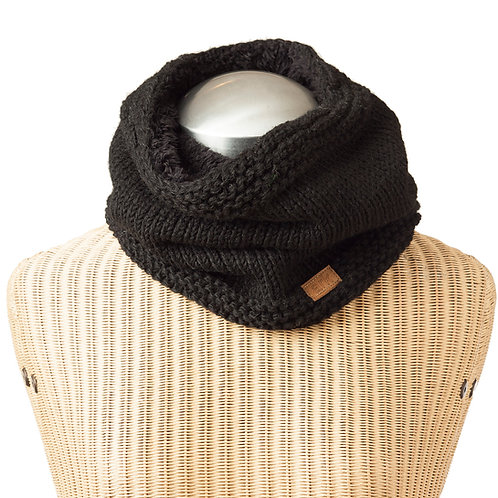Black knit tube shaped neck warmer on a mannequin, loose enough to fall in folds