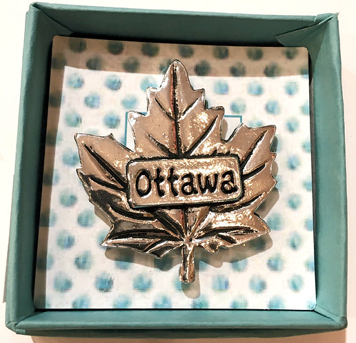 Blue box holding pewter magnet maple leaf shape with engraved word 'Ottawa'