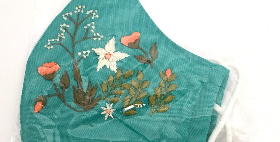 Side view of folded turquoise embroidered mask with elegant forest of peach, cream & green flowers