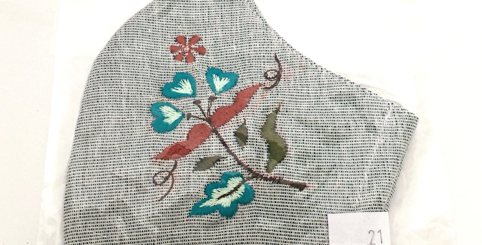 Side view of folded light gray embroidered mask with turquoise, rust, olive & cream floral design
