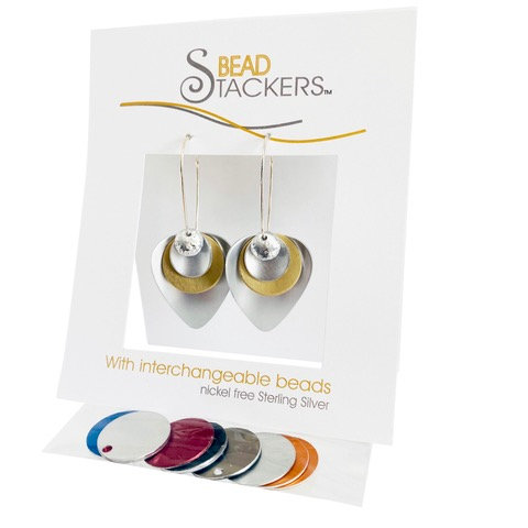 White card holding pair of silver & disk earrings with attached bag of interchangeable metal disks