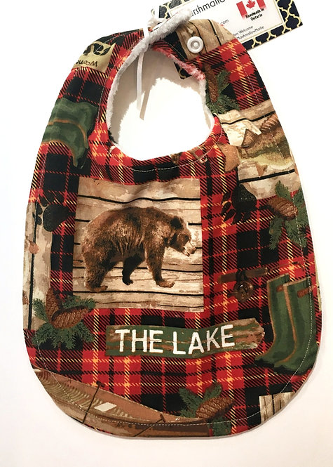 red & black plaid oval-shaped cloth baby bib with brown bear and white lettering 'THE LAKE'