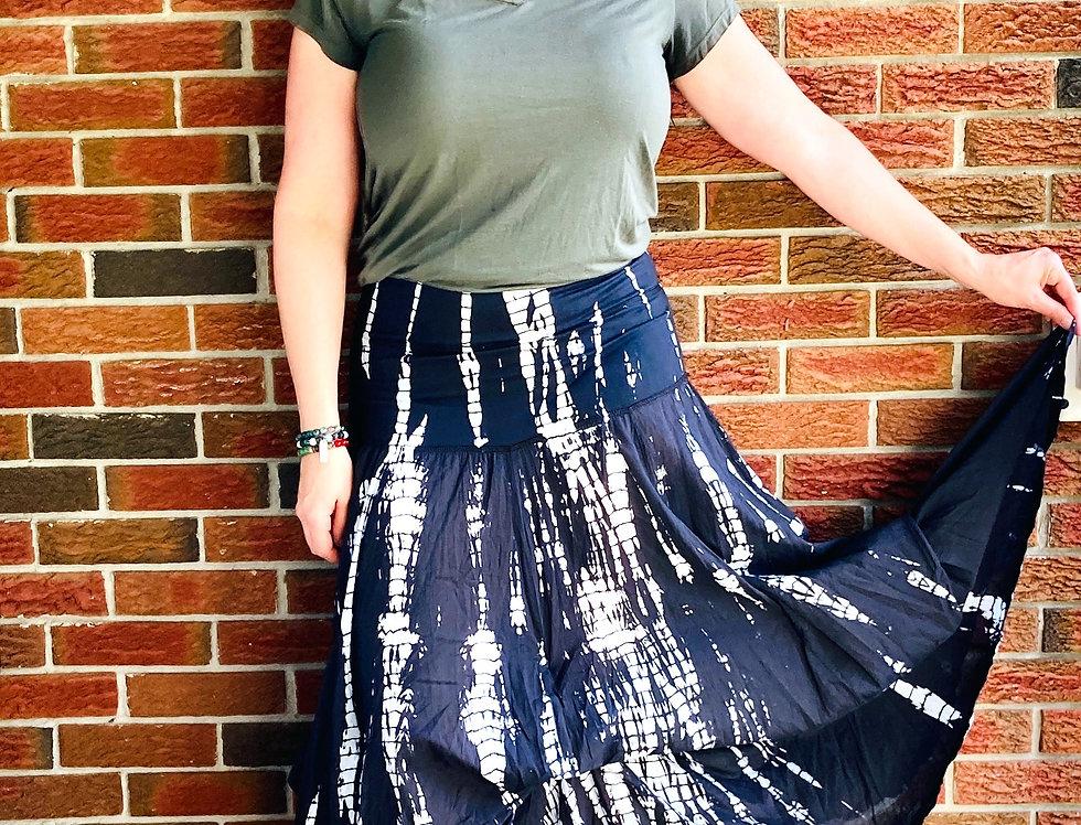 Model holding up one corner of hem of black & white tie-dye full length skirt