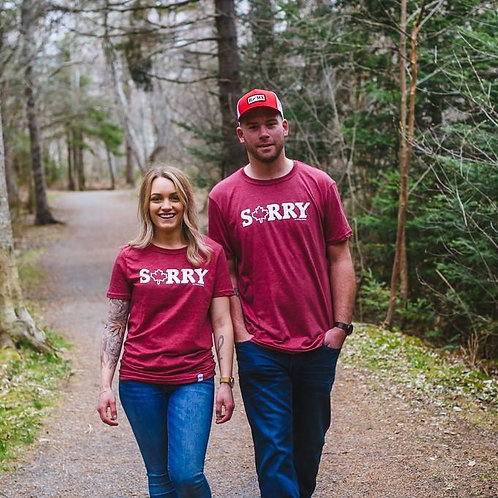 Man and woman walking on a tree-lined road both wearing My Home Apparel Sorry T-Shirt in heather red