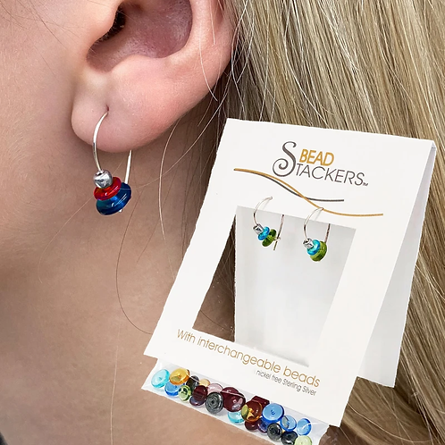 Woman wearing silver earrings with silver, red & dark blue beads & package of interchangeable earrings - many colors of beads