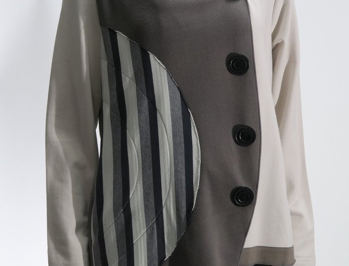 Cream & gray fleece jacket front right panel cut in half-circle-decorative buttons, black gray cream stripes on 1 side