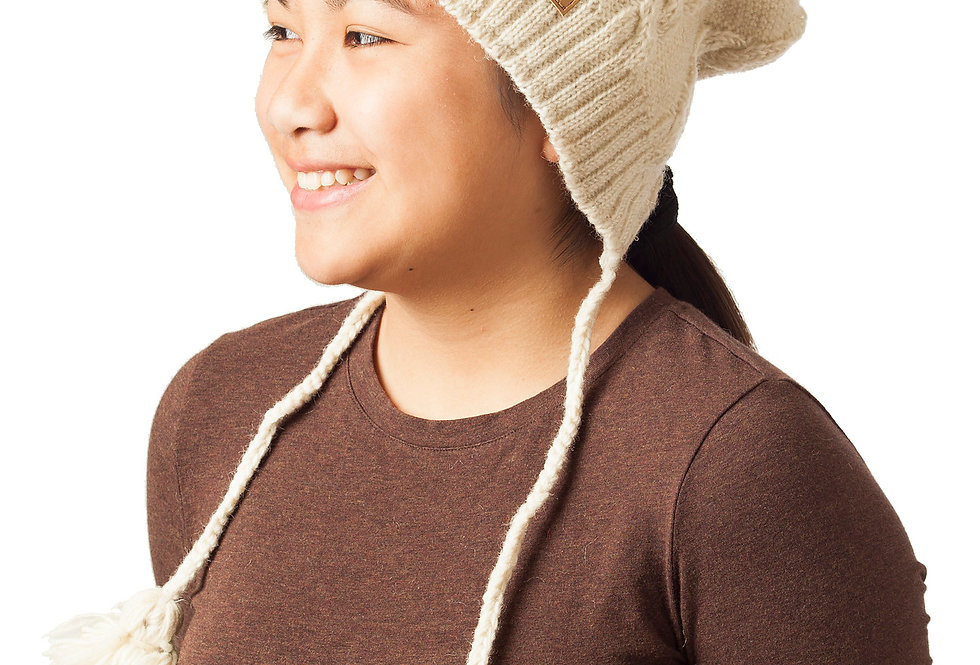 White cable knit toque with pompom & braided wool cords on either side tipped with pompoms