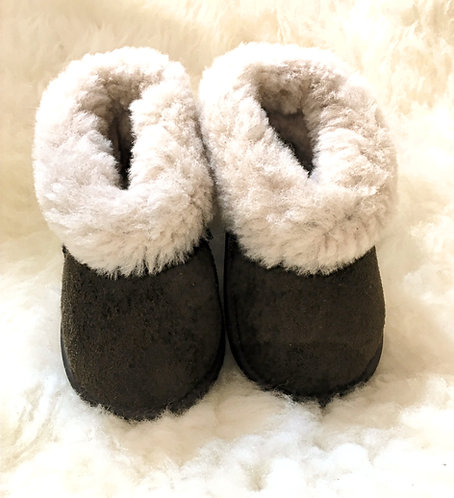 Front view of kids brown sheepskin slippers with natural white fleece interior showing on turned back cuffs