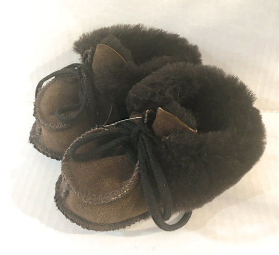 Side view of pair of baby's brown sheepskin slippers with laces