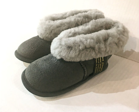 left view of pair of gray sheepskin slippers with fleecy tops turned down at the ankle