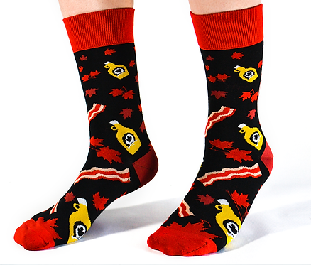 Pair of feet wearing black socks printed with yellow bottles of maple, red & white strips of bacon & red maple leaves