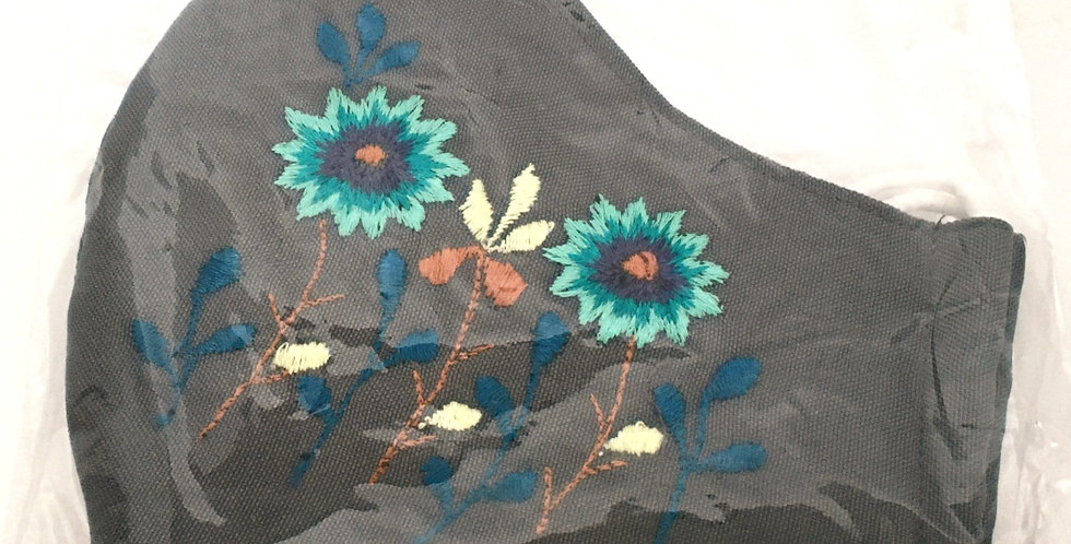 Side view of folded blue-gray embroidered mask with 2 turquoise flowers on tawny stems with aegean blue accents