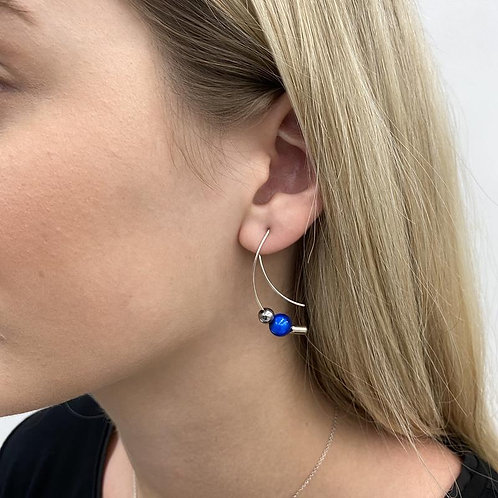 Woman wearing long curved silver earring with silver and blue beads