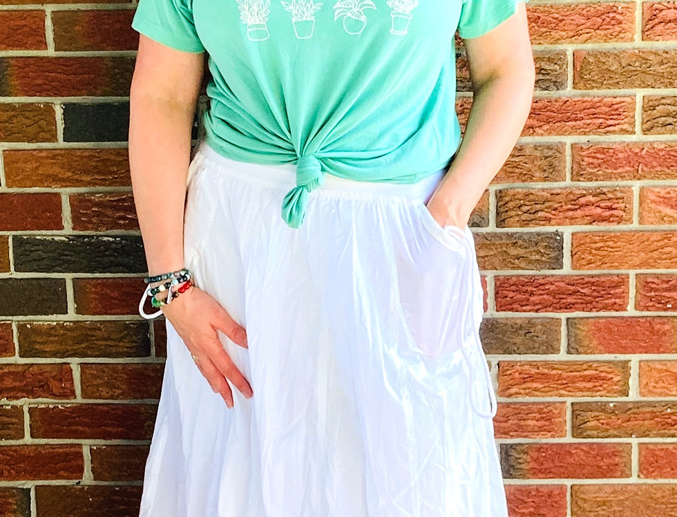 Front view of model wearing full white skirt with roomy pockets on sides