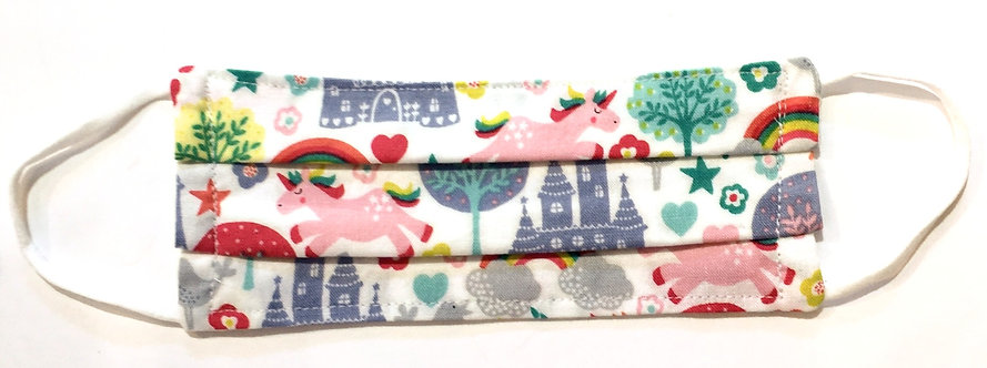 Tiny white cotton mask laid flat with print of pink unicorns & blue castles & green trees