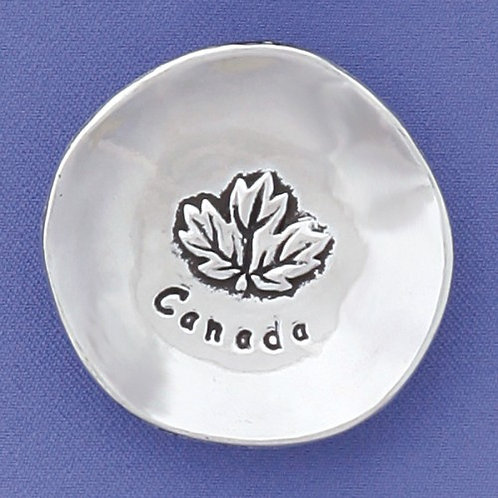Little pewter bowl with Maple Leaf and the word Canada inside on blue background
