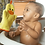 Baby in bathtub gazing at bright yellow and orange terry cloth bath mitt with duck face