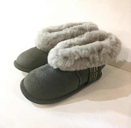 Side view of pair of kids gray sheepskin slippers with fluffy white cuffs