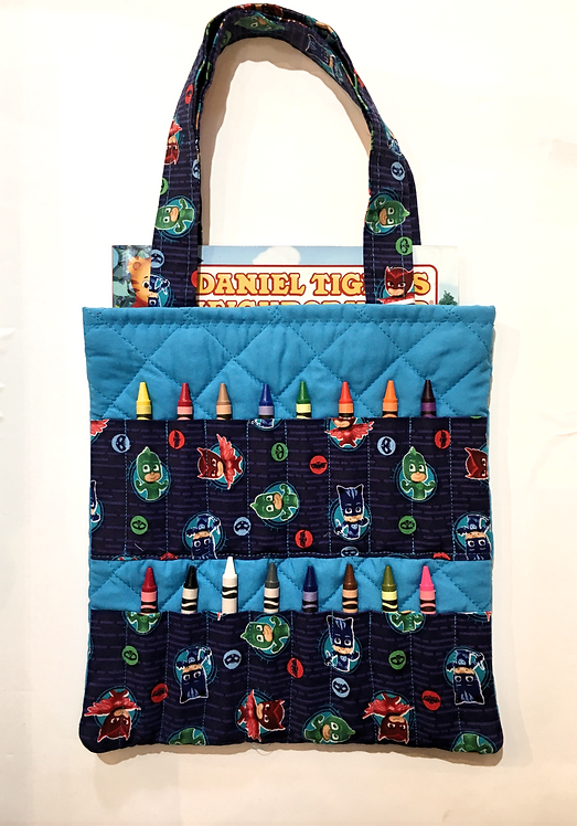 Flat rectangular teal blue cotton tote bag holding coloring book and 16 slots on the front holding crayons