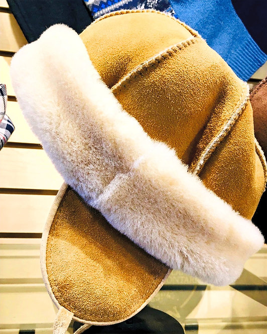 Side view of kids' tan sheepskin hat with natural white fleece cuffed brim and earflaps