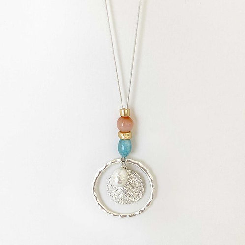 Necklace with round silver colored metal pendant enclosing sand dollar charm - coral & turquoise beads above pendant