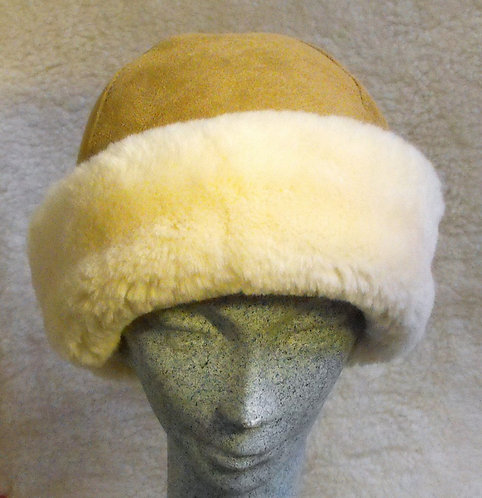 Front view of tan sheepskin hat with wide brim turned back all around showing fleecy golden white interior