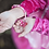 Close up of child in hot pink dress holding hot pink butterfly bracelet