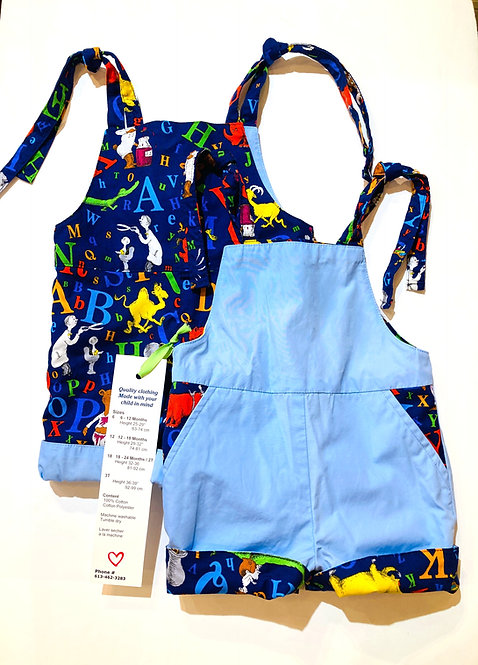 2 pairs of reversible baby sized overall shorts, 1 navy with ABC print, the other light blue