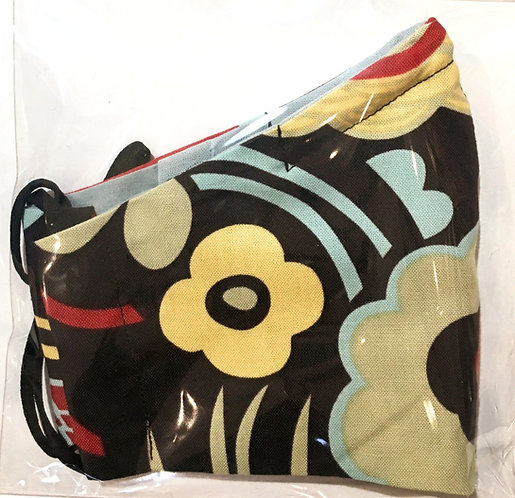 Close up of black mask with yellow, red & green flowers print folded in half in plastic