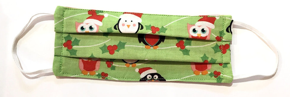 Tiny green cotton mask laid flat with black & red penguins & snowmen & holly print