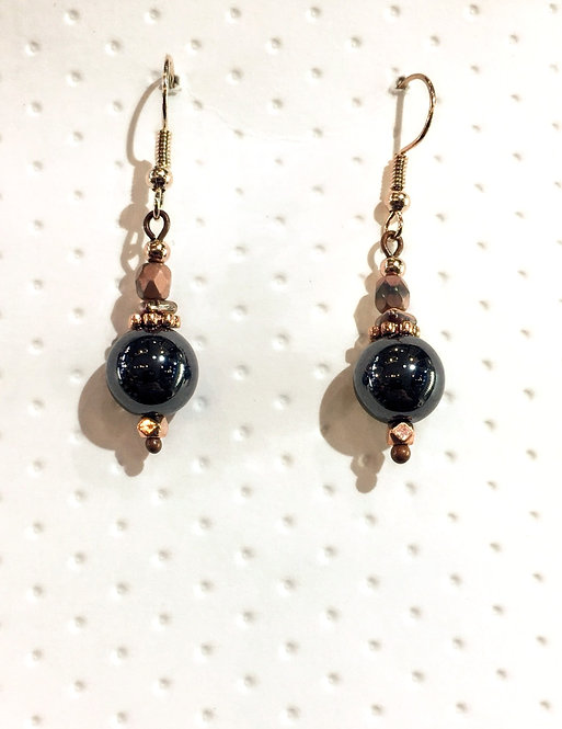 Pair of rose gold colored earrings with round black 10mm stones