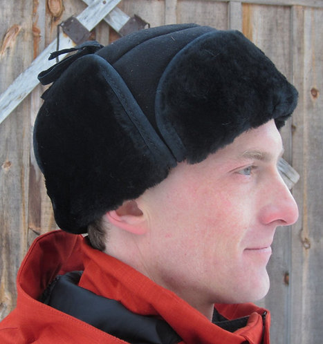 Man wearing black Sheepskin Yukon style Hat side view, earflaps turned up and tied on top of head