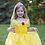 Little girl playing outdoors in yellow princess dress and bejeweled tiara.