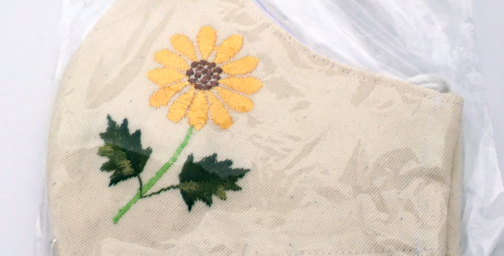 Side view of folded cream embroidered mask with bright & cheerfulyellow sunflower and green leaves