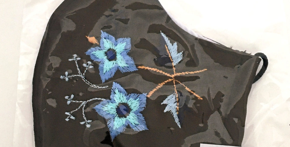Side view of folded dark chocolate brown cotton mask with embroidery of two periwinkle & aqua flowers