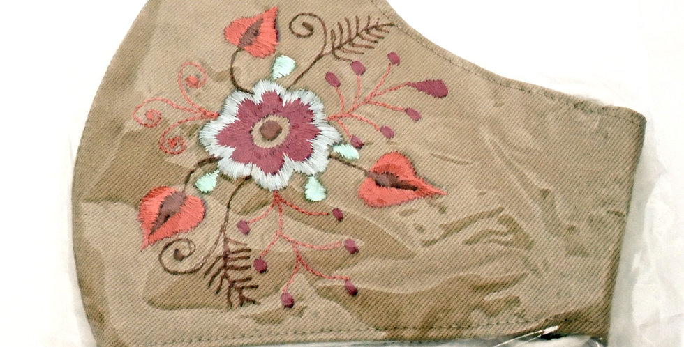Side view of folded embroidered latte cotton mask- currant & white flower & spray of salmon, bronze, currant & brown details