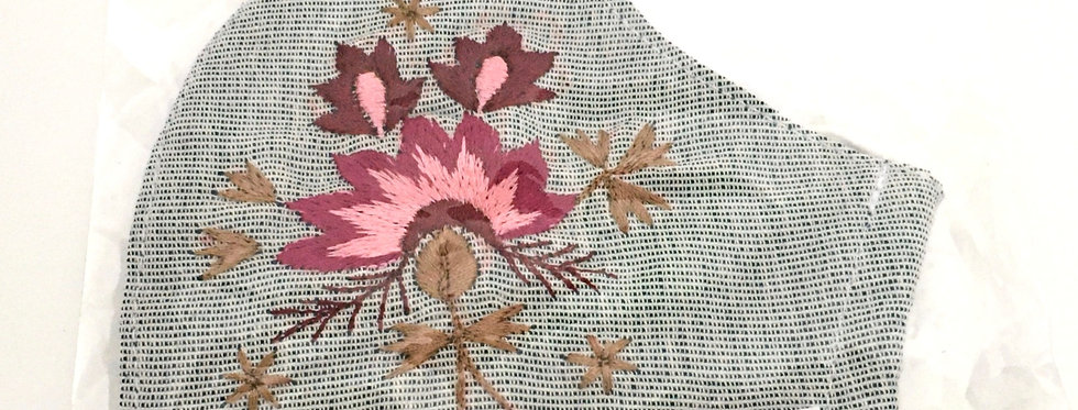Side view of folded light gray embroidered mask with pink, currant, garnet & ecru floral design