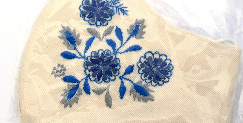 Side view of folded cream embroidered mask with bright blue, indigo & silver gray floral pattern