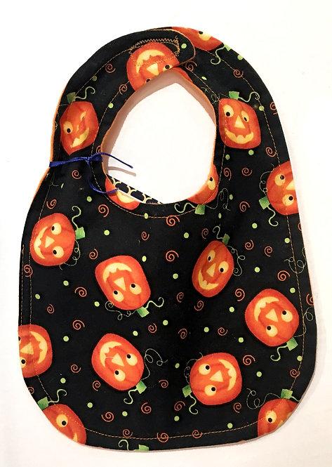 Oval shaped black cotton baby bib with orange smiling carved pumpkins print