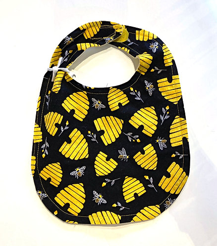 Black oval shaped cotton bib with print of yellow bee hives
