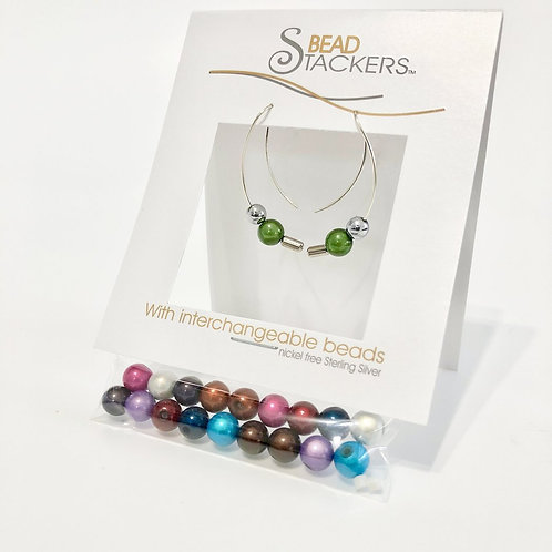 Package of interchangeable  long curved silver earrings with green beads and bag of many colored beads