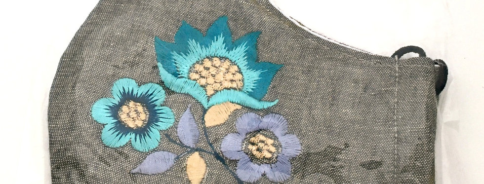 Side view of folded gray embroidered mask with light & darkturquoise, mauve & pale yellow flower arrangement
