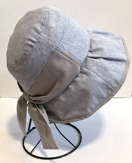 Side view of gray sun hat on stand with long brim & bow at the nape