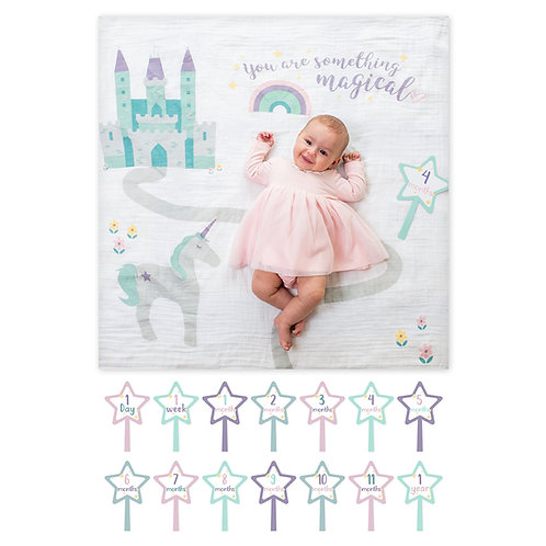 Baby lying on white blanket with castle & unicorn print & 14 star-shaped cards