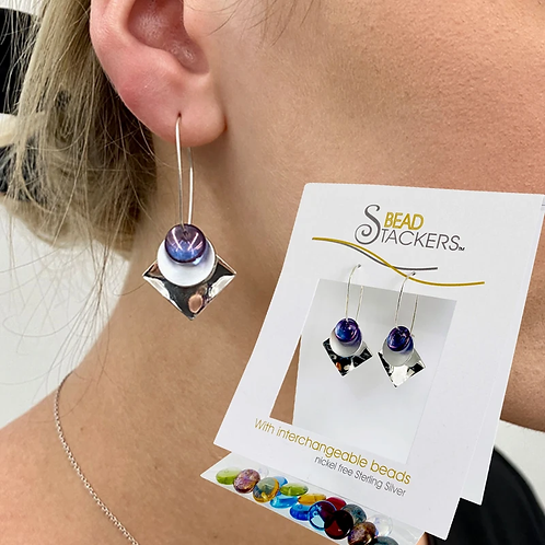 Woman wearing silver earrings with colored bead, round disk and square disk and same earrings in package with more beads