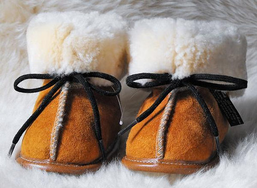 Front view of tan sheepskin slippers-natural white fleece interior-black laces