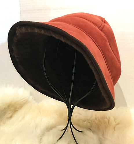 Front view of red Zelda paneled sheepskin hat with small peaked brim