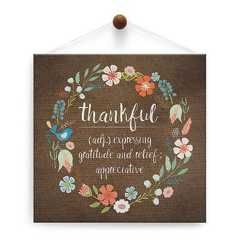 hanging brown square canvas card with floral wreath around text 'thankful (adj) expressing gratitude & relief; appreciative'