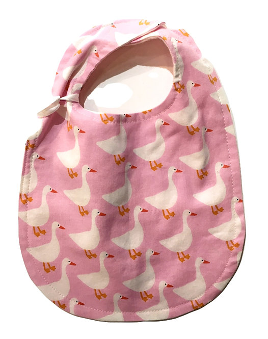 Pink oval shaped cotton bib with print of white geese