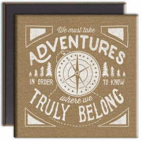 Kraft-brown canvas magnet with white lettering that reads we must take adventures in order to know where we truly belong